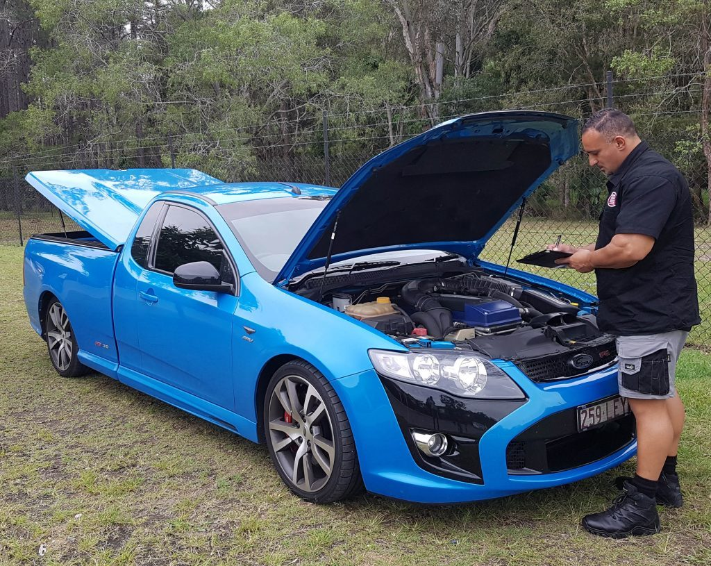 man infront of blue car doing inspection